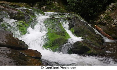 Waterfall Over Mossy Rocks - River water falling over mossy...