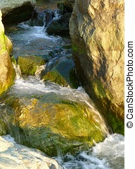 Waterfall through mossy rocks along the coast