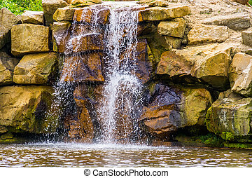 waterfall with large boulders, Beautiful garden architecture, nature background of streaming water