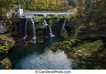 waterfalls and a reservoir with rock crevice and green plants in the nature