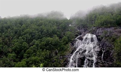 Waterfalls in a foggy mountain