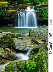 Waterfalls in green forest during a summer, exposure with a long