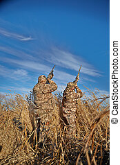Waterfowl hunters aiming up into sky on sunny day - Two...