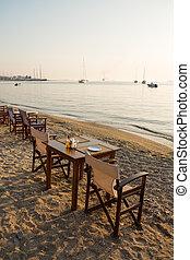 Waterfront cafe table on sandy beach, Paros island, Greece