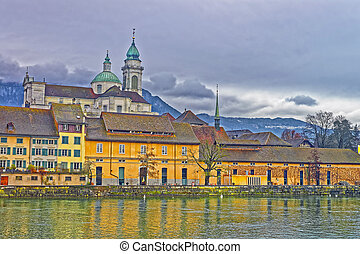 Waterfrontof Saint Ursus Cathedral in Solothurn. Solothurn is the capital of Solothurn canton in Switzerland. It is located on the banks of Aare and on the foot of Weissenstein Jura mountains