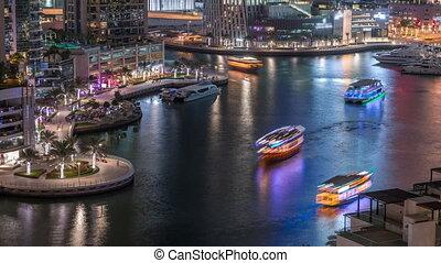 Waterfront promenade in Dubai Marina aerial night timelapse. Boats and yachts floating on canal. Dubai, United Arab Emirates