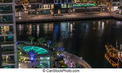 Waterfront promenade with swimming pool in Dubai Marina aerial night timelapse. Boats and yachts floating on canal. Dubai, United Arab Emirates