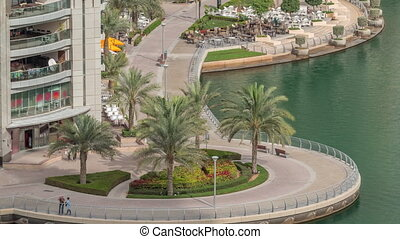 Waterfront promenade with palms in Dubai Marina aerial timelapse. Boats and yachts floating on canal. Dubai, United Arab Emirates