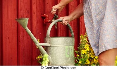 Watering can - Filling a watering can.