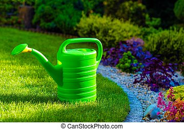 Watering Can in a Garden - Green Plastic Watering Can in the...