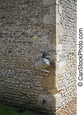 Watering can. - Old watering can hanging on a church stone...