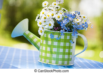 Watering can with daisy flowers