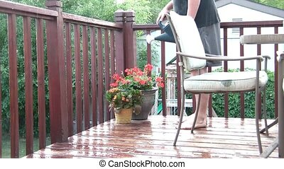 Watering Flowers in Rain Irony - Man stands on deck in and...