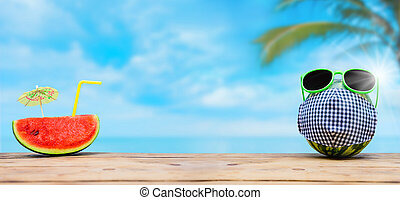 Watermelon with sunglasses and face mask on summer beach background. Social distancing at least 2 metres or 6 feet away from other.