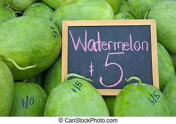 Watermelons on display with a sign in Rarotonga market Cook...