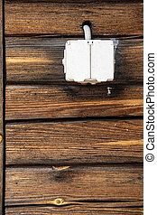 Waterproof electrical outlet with a closed lid, on the log wall of the house, outdoors.