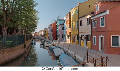 Waterside street with brightly painted houses and walking...