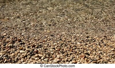 waterside with pebble stones - waves at a lake with pebble...