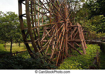 Waterwheel front of entrance to Huanglong cave in China. -...