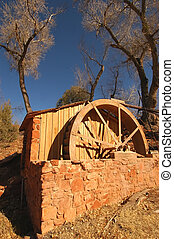 Rustic old waterwheel in Sedona, Arizona - with blue sky and trees