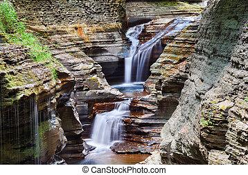 Watkins Glen waterfall in woods with rocks and stream in...
