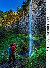 Watson Falls Backpacker in Oregon - Girl Backpacker taking...