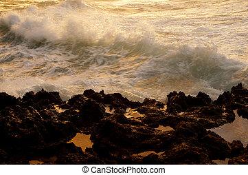 Wave break along rocky shore at Dusk