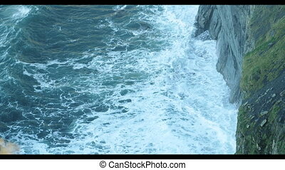 Wave breaking against cliff in Irel