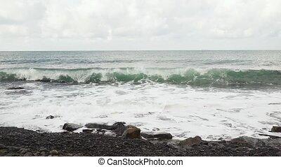 Wave breaks against the rocks slow mo