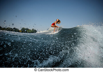 Wave in front of attractive blonde girl riding on the red wakeboard