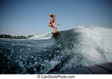 Wave in front of blonde girl riding on the red wakeboard
