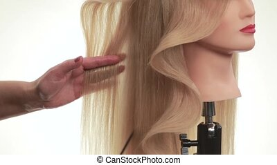 Wave of hair on the head of the dummy. Hairstyle on a mannequin turned in profile, beautiful wave like the option hairstyles for long hair, on white background, close up