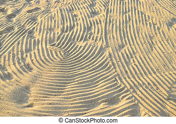 Wave patterns in the sand on the beach under the sun