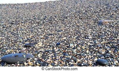Wave runs on pebble beach sea shore