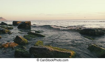 Wave splash on boulders in the water at sunset slow motion