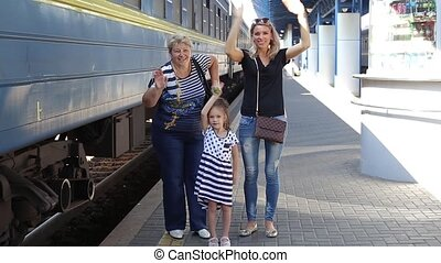 waves a hand goodbye - family at the train station waving...