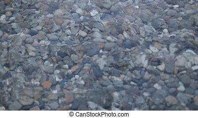 Waves and clear water. Through the water are visible stones. Rivers, lakes and the sea.