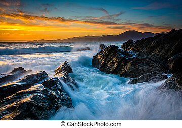 Waves and rocks in the San Francisco Bay at sunset, seen from Baker Beach, San Francisco, California.