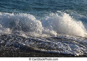 Waves and sea foam on the coast