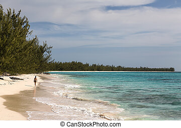 A woman walking along the shoreline with waves and turquoise water near the Orange Creek area of Cat Island, Bahamas.
