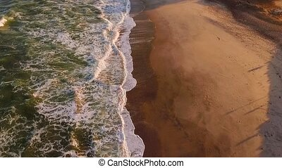 Waves arrive on the beach of Namibia in the rays of the...