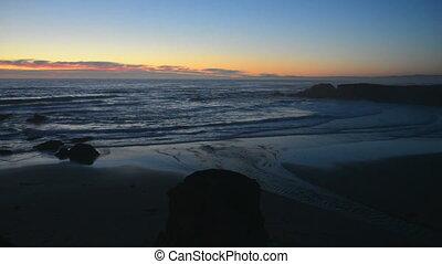 Waves at the beach at sunset
