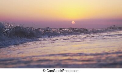 Waves at the beach in slow motion during amazing sunset.