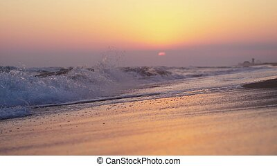 Waves at the beach in the evening at sunset
