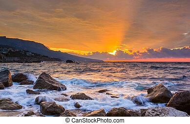 sunrise over the sea - Waves break about stones at sunrise...