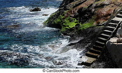 Waves break about the rocky coast of the azure coast, ...