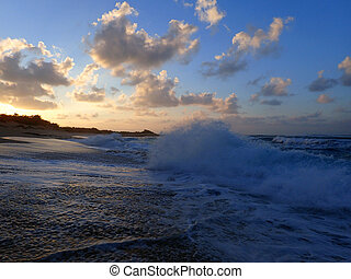Waves break on shore of Hanakailio Beach with dramatic blue-pink cloudy skyline at dusk