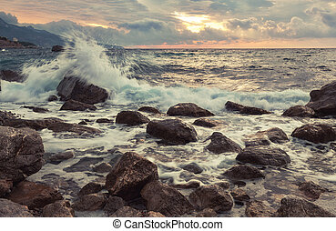 Waves break with splashes about big stones at sunrise, the...