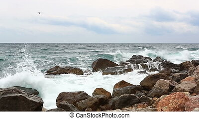 Waves break with splashes about big stones