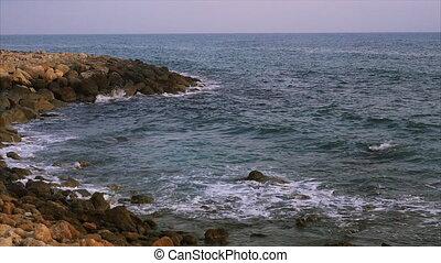 Waves breaking against rocks on sea shoreline.